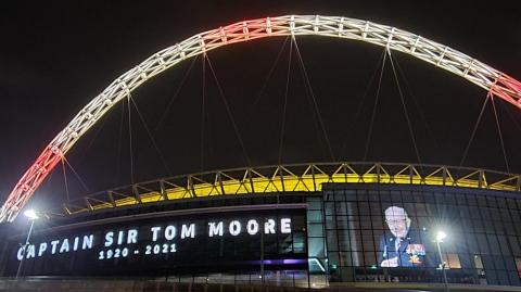 Estadio de Wmbley encendió sus luces en honor al capitán Tom Moore.